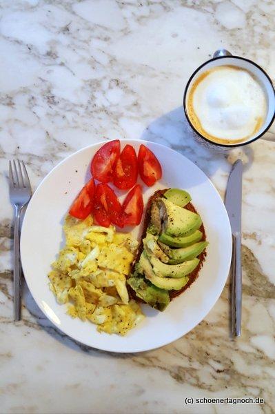 Frühstück mit Rührei, Avocado-Brot, Tomaten und Cappuccino