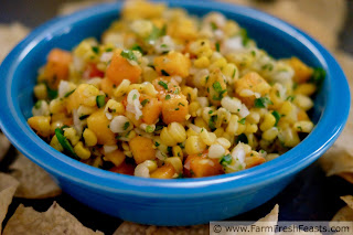 a bowl of fresh peach and corn salsa with chips
