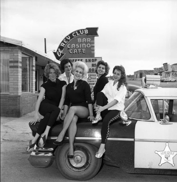 Five working women pose on a police car in front of the El Rey Club in Searchlight, NV. Hey Ladies. marchmatron.com