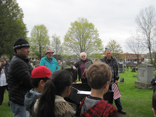 Man and woman talking to a group of students in a cemetery