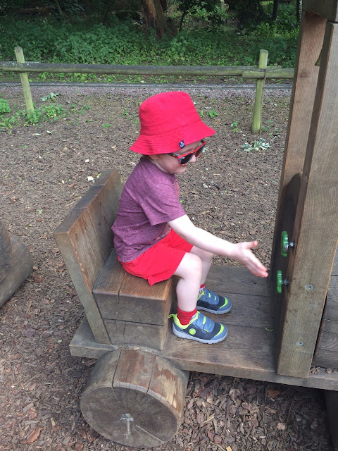 Child sitting on a wood train in a play area