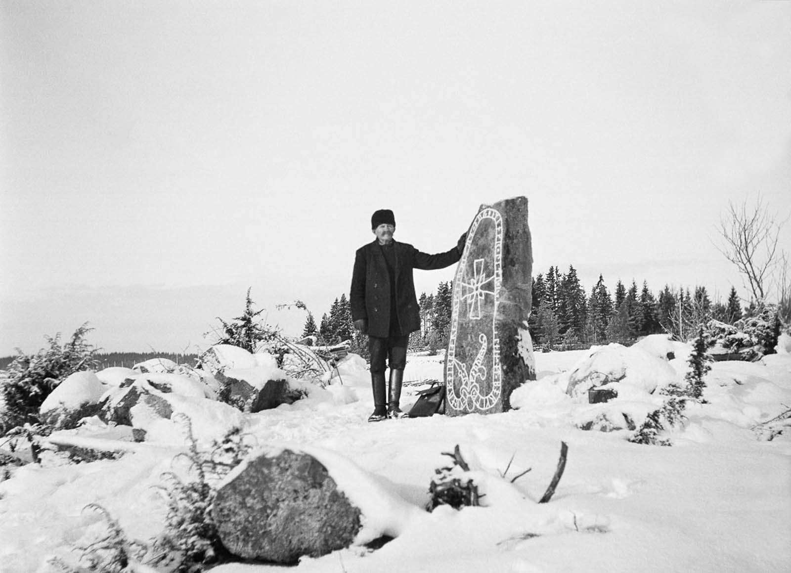 A man stands with a runestone in Odensala. The stone reads,