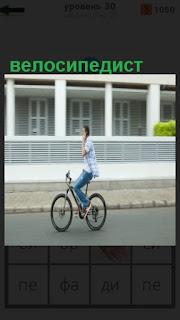 на велосипеде едет парень без рук, велосипедист катается