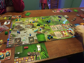 A game of Architects of the West Kingdom in progress. The board is laid out on the table, with player mats, cards, tokens, and meeples around the board and in various places on the board itself.