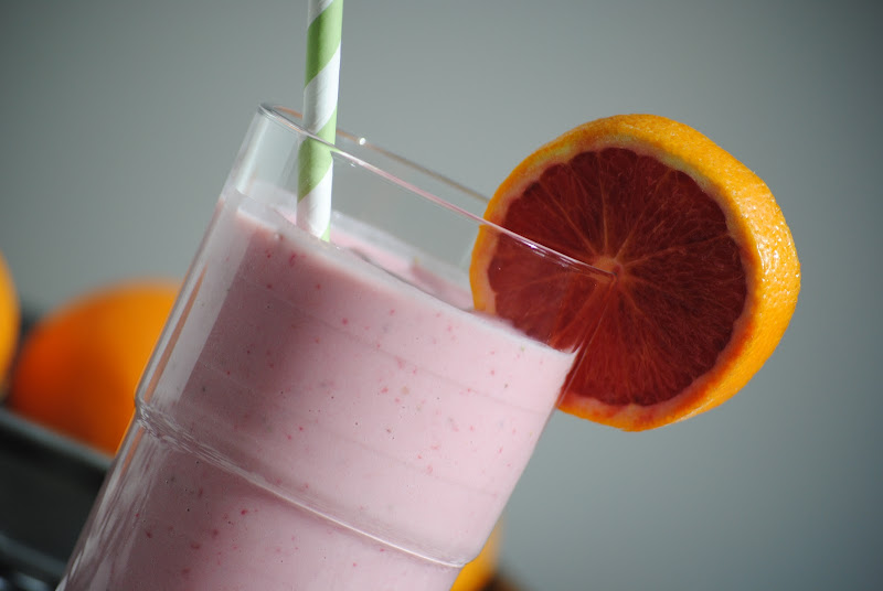 Fruit smoothie with straw and fruit slice