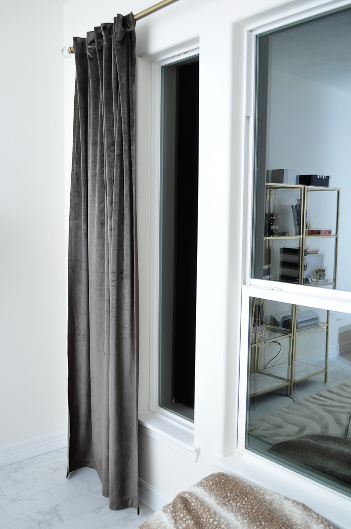 Gray velvet drapes on a brass curtain rod in a home office.