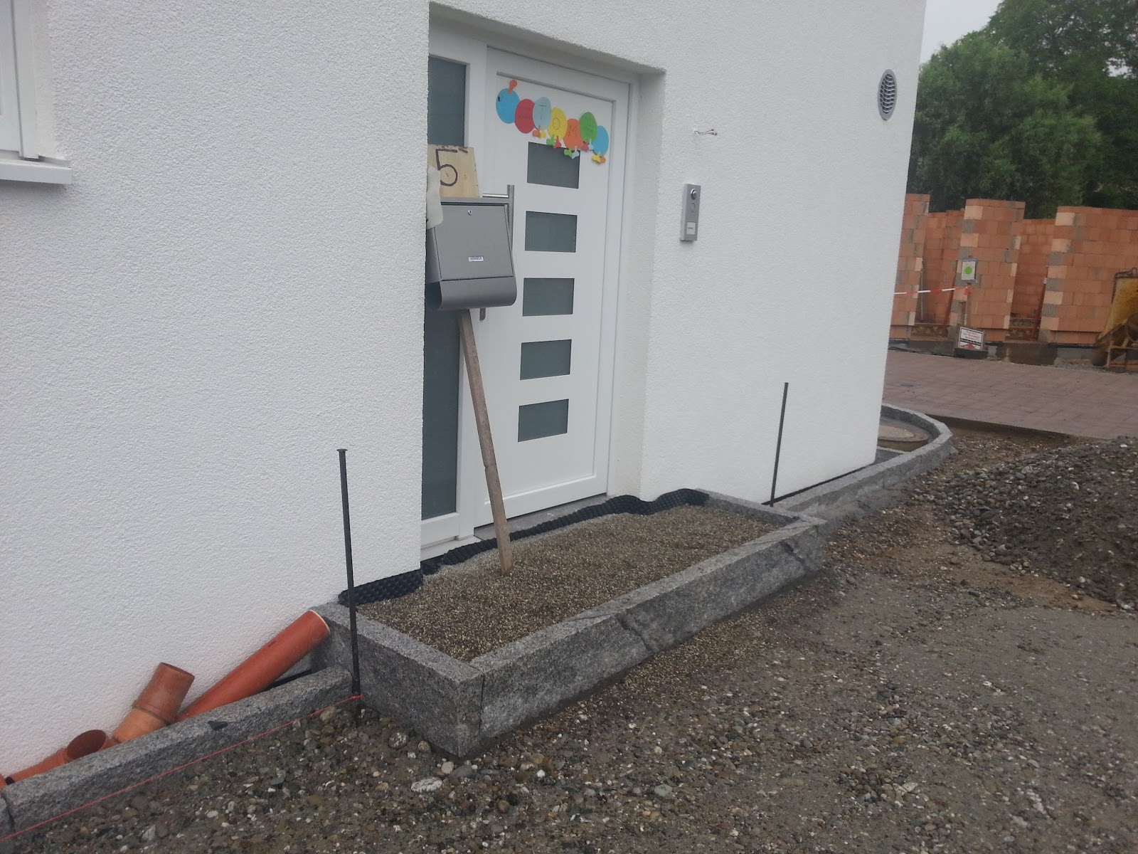 wir bauen ein okal haus steingarten mit granitsteinen eingefasst hof vorbereitet. Black Bedroom Furniture Sets. Home Design Ideas