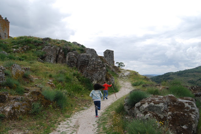 Dos niños corriendo por un camino que asciende hacia el castillo de Trevejo