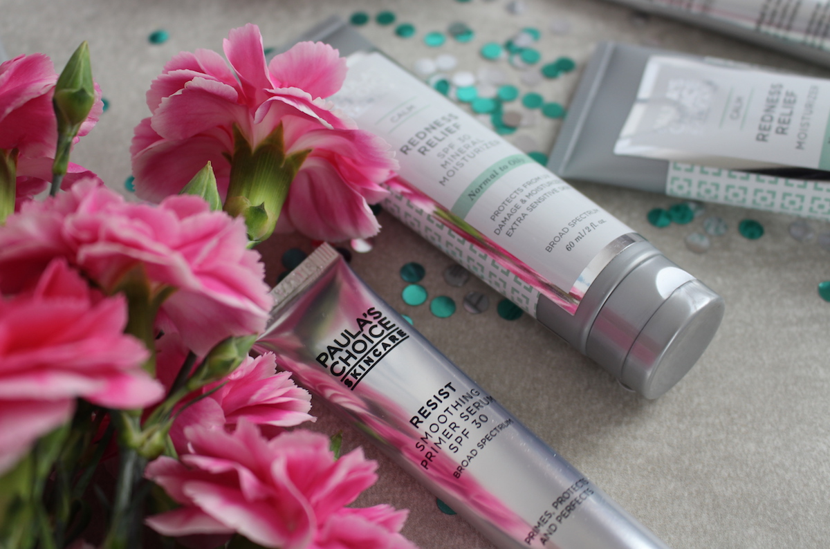 This is a close up of Paula's Choice skin care products, surrounded by beautiful pink flowers.