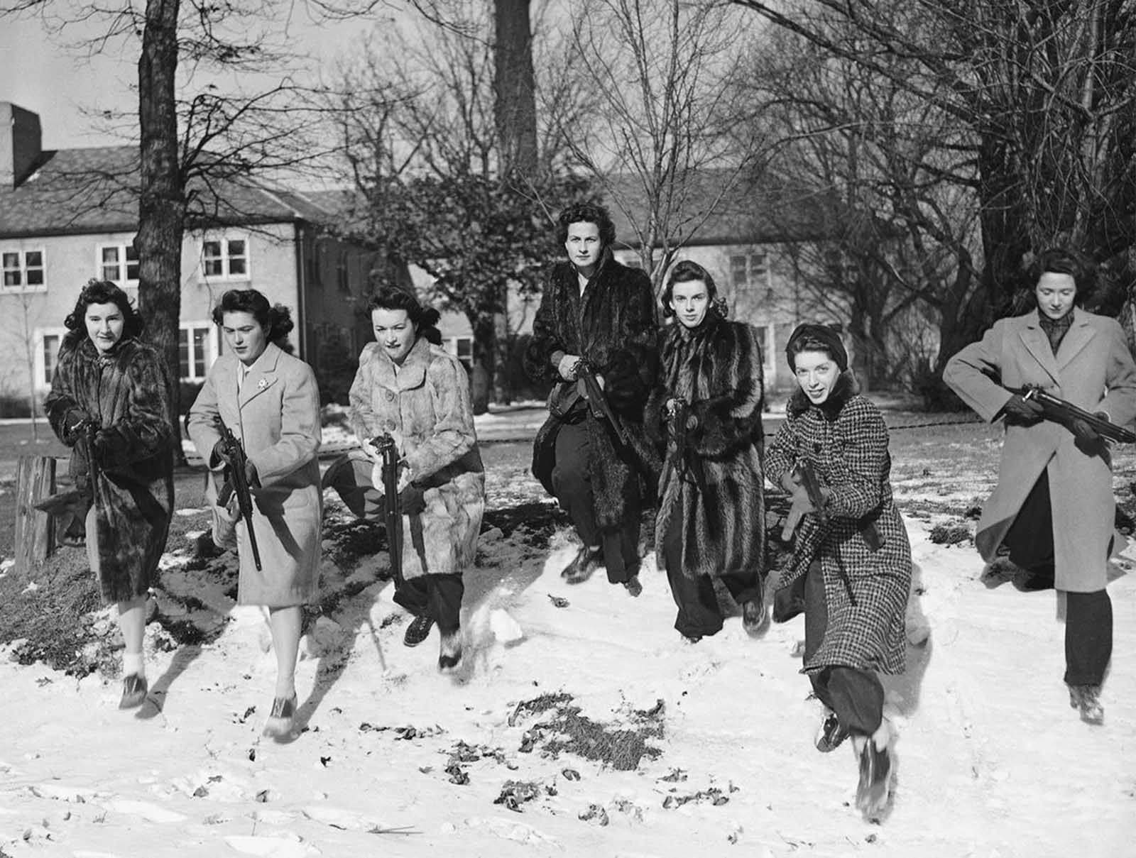 These Northwestern University girls brave freezing weather to go through a Home Guard rifle drill on the campus in Evanston, Illinois on January 11, 1942. From left to right are: Jeanne Paul, age 18, of Oak Park, Illinois,; Virginia Paisley, 18, of Lakewood, Ohio; Marian Walsh, 19, also from Lakewood; Sarah Robinson, 20, of Jonesboro, Arkansas,; Elizabeth Cooper, 17, of Chicago; Harriet Ginsberg, 17.