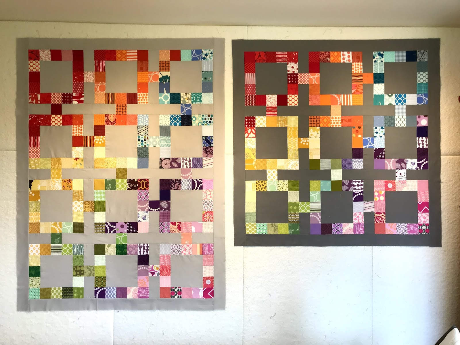 Rainbow scrap quilts on a design wall in baby sizes