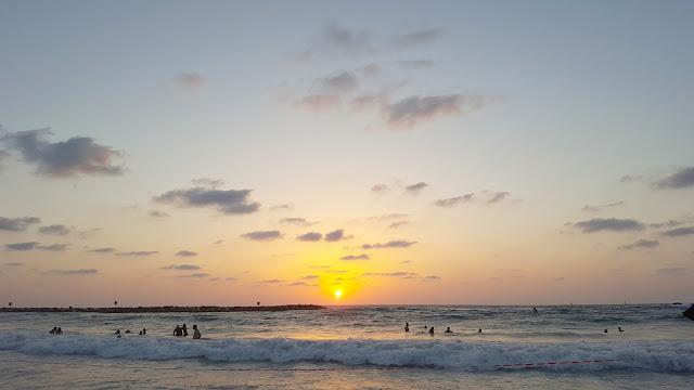 השמש כעט ונכנסת לים בחוף גורדון לקראת ערב