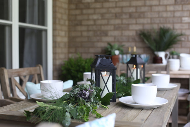Outdoor dining table with lanterns and dishes close up