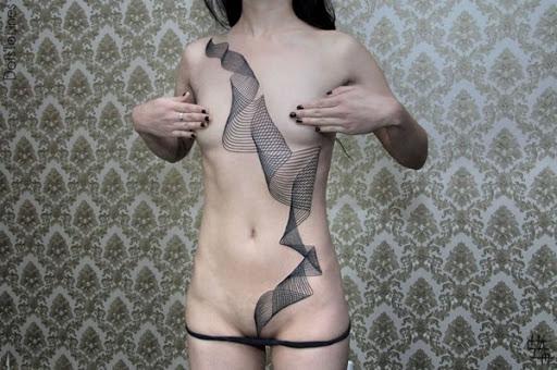 Uma série de rolagem linhas começam em que o portador do ombro esquerdo e desça para sua virilha neste tatuagem.