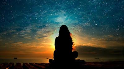 Mujer meditando frente a una puesta de sol