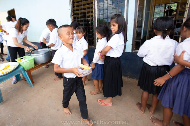 Cambodian boy is super excited to receive his lunchtime meal of rice, egg and pineapple.