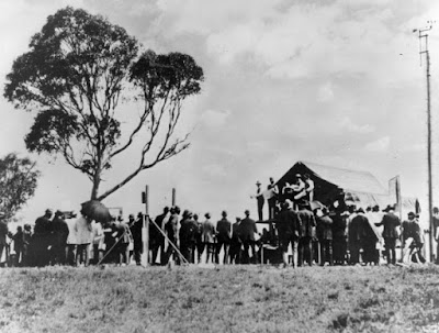 The first land auction in the ACT, 12 December 1924. On the platform, from left are:  J. H. Calthorpe, H. C. Crammond, W. G. Woodger, Sir Austin Chapman and T. E. Woodger.  Source: #003693, Images ACT,
