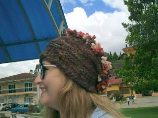 gorro de lã       marrom           na cabeça de uma moça de óculos