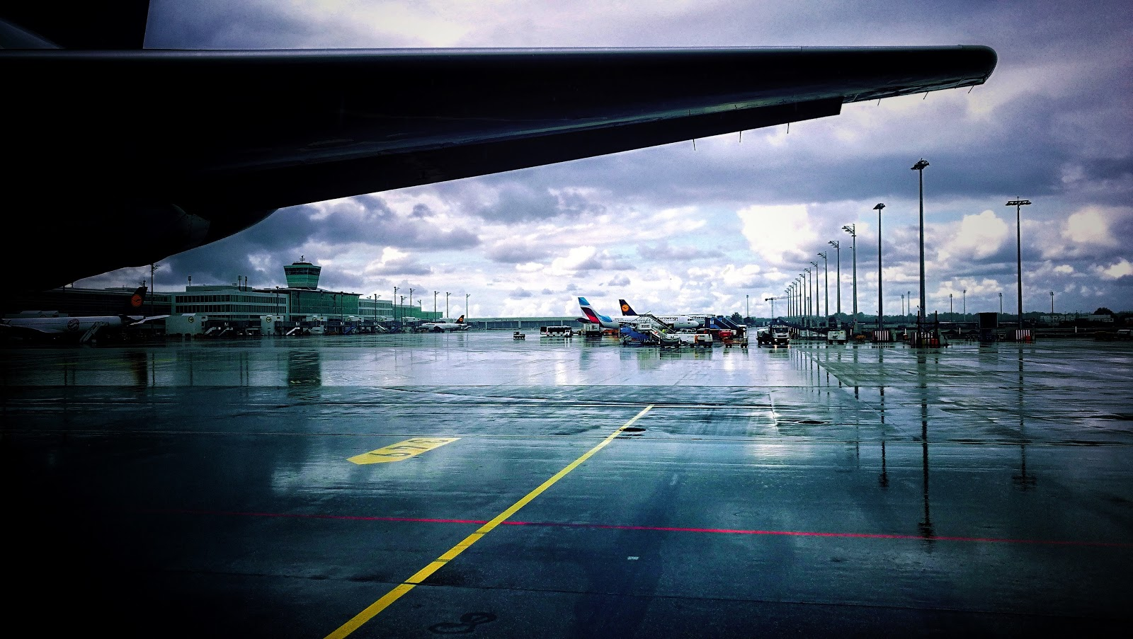 München Flughafen mit Blick auf das Terminal - Flugzeuge im Vordergrund bei Regen