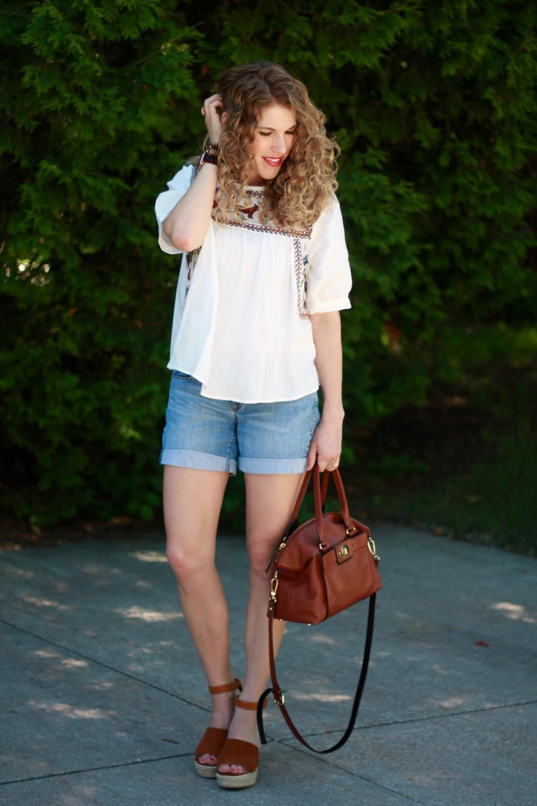 white embroidered blouse, denim shorts, wedges, cognac accessories