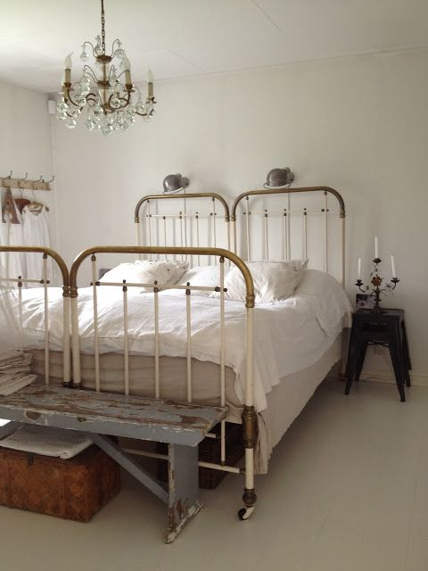 Gorgeous farmhouse style bedroom with vintage twin beds pushed together and crystal chandelier
