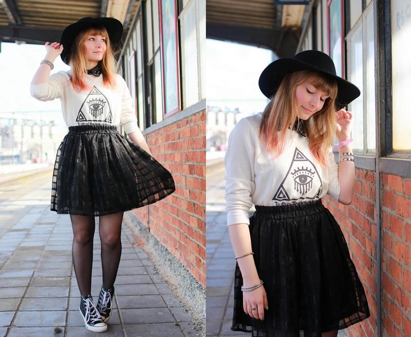 Tenue noir et blanche avec un pull imprimé Illuminati et une jupe en transparence