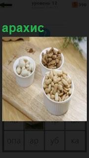 На столе стоят три чашки с орехами, в одной из них находится арахис