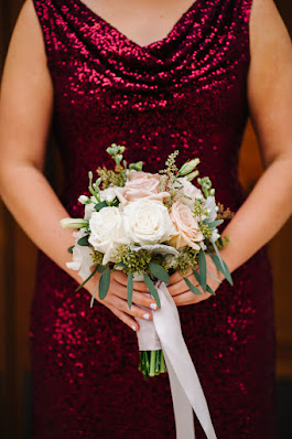 maid of honor in deep red sequin dress holding bouquet