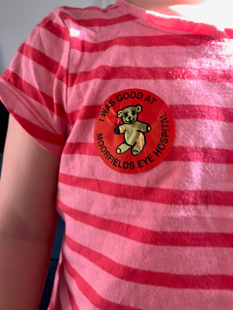 "A close up on a striped t-shirt and a sticker with ""I was good at Moorfields Eye Hospital"" with a picture of a teddy bear"