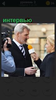 журналисты берут интервью с микрофоном и камерой