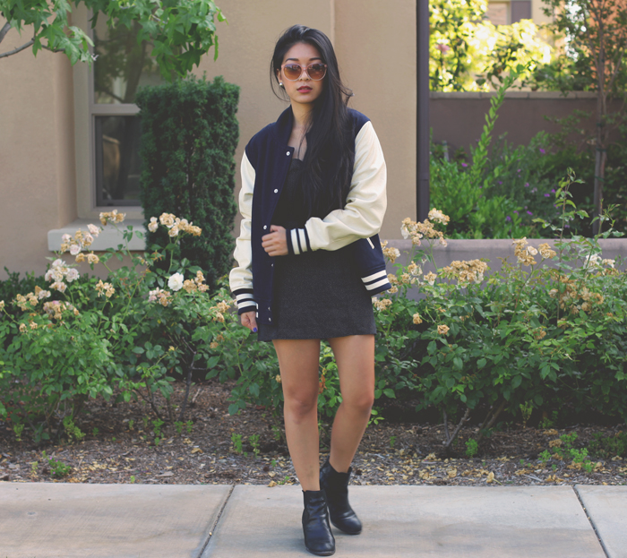 Stephanie Liu of Honey & Silk wearing Urban Outfitters varsity jacket, Reformation web dress, Aldo sunglasses, and Dolce Vita boots