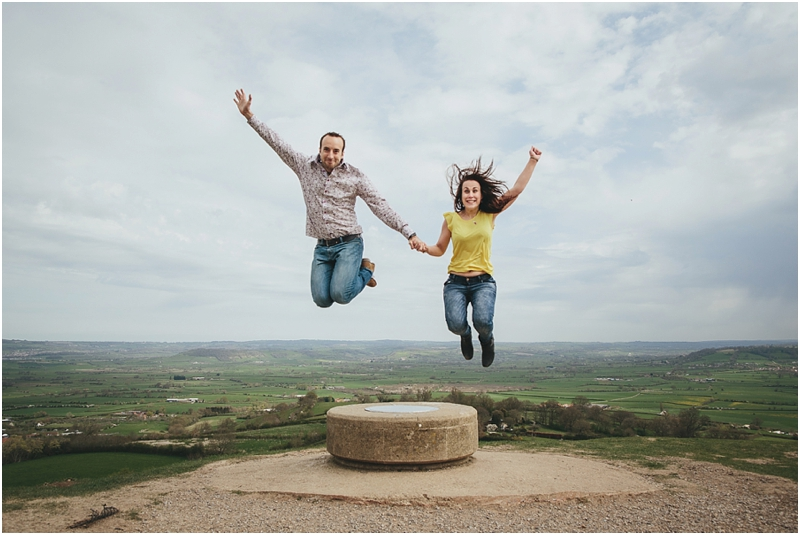 A couple leaping in the air at Glastonbury Tor