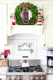 Boxwood wreath with decorative chalkboard wreath for Christmas on kitchen mantel