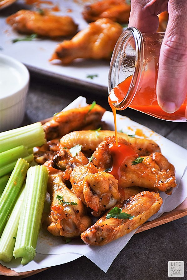Extra buffalo wing sauce being poured onto chicken wings ready to serve and enjoy for game day