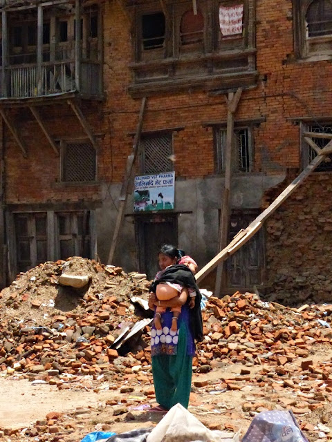 Young woman with a child standing in front of earthquake damaged house in Sankhu, Nepal