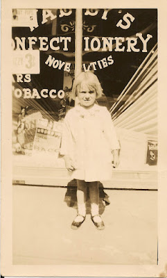 "Mary E. Dixon standing in front of her father's candy store, ""Wally's Confectionary."" Around 1930. Marshall Street, Elizabeth, NJ."