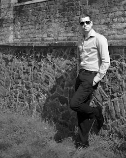 shirt and trousers leaning against a wall black and white