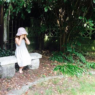 Girl in garden covering her eyes