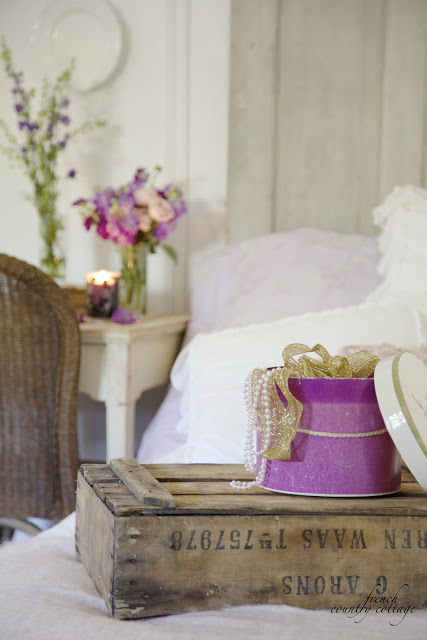 Ribbons in a hat box on the bed with flowers and a candle on the nightstand