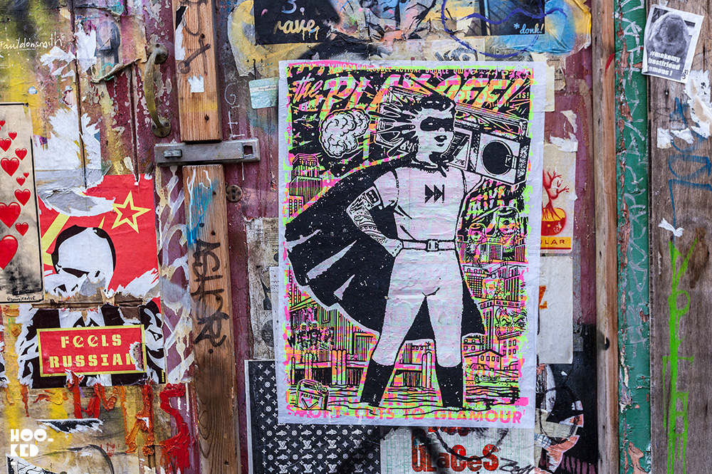 Super hero with boombox, Brick Lane Street Art paste-ups in London by artist Zombiesqueegee
