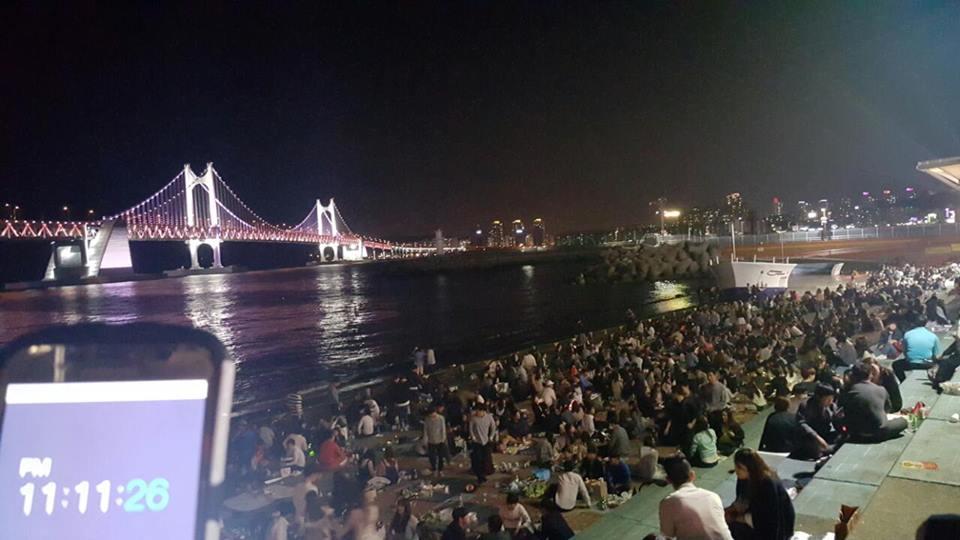 Jóvenes coreanos comiendo y bebiendo por la noche frente al mar