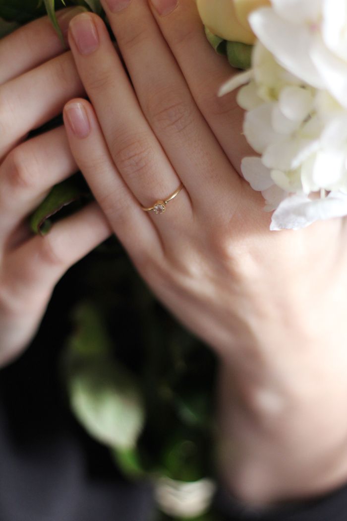 Hands holding flowers with engagement ring