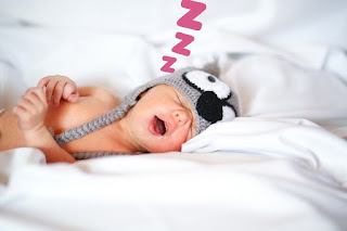 An image in which a kid is sleeping with his mouth open