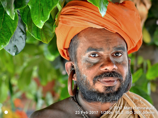 matt hahnewald photography; facing the world; gorakh nath; monk; monastery; bhavnath; bhavnath fair; character; face; earrings; ears; holed; eyes; facial expression; eye contact; full beard; turban; orange; consent; empathy; rapport; respect; traveling; religious; traditional; cultural; hinduism; festival; event; mela; devotee; pilgrim; junagadh; gujarat; asian; indian; western india; one person; male; middle-aged; man; picture; photo; face perception; physiognomy; educational; nikon d3100; nikkor af-s 50mm f/1.8g; prime lens; 50mm lens; 4x3 aspect ratio; horizontal orientation; street; portrait; closeup; headshot; seven-eighths view; outdoors; color; posing; authentic; smiling; powerful; kanphata; yogi; darshani; gorakhnathi; shaivism; big; splitted ears