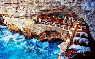 Este lugar existe e se chama Grotta Palazzese em Polignano a Mare, uma cidade situada na costa adriática da Puglia, no sul da Itália. Foto: vista aérea de um restaurante construído dentro de uma gruta: entre o paredão com saliências irregulares na parte superior, uma tímida fenda à esquerda usada como corredor e as rochas corroídas pela erosão na parte inferior, onde percebe-se as espumas brancas das ondas do mar azul anil em repuxo, surge o restaurante, à direita, em um nível acima cinco mesas retangulares, toalhas brancas, em cada coluna baixa quadrangular da mureta, há uma luminária com cúpula arredondada que remete a um cogumelo, iluminação delicada sem interferência na arquitetura natural; ao fundo, em um nível mais baixo, um amplo vão protegido pela rocha em arco, mesas, cadeiras e luminárias no mesmo estilo compõem o espaço e criam uma atmosfera romântica.