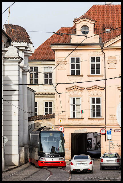 Tram 9251 heads into a tunnel under a building in Lesser Town Prague