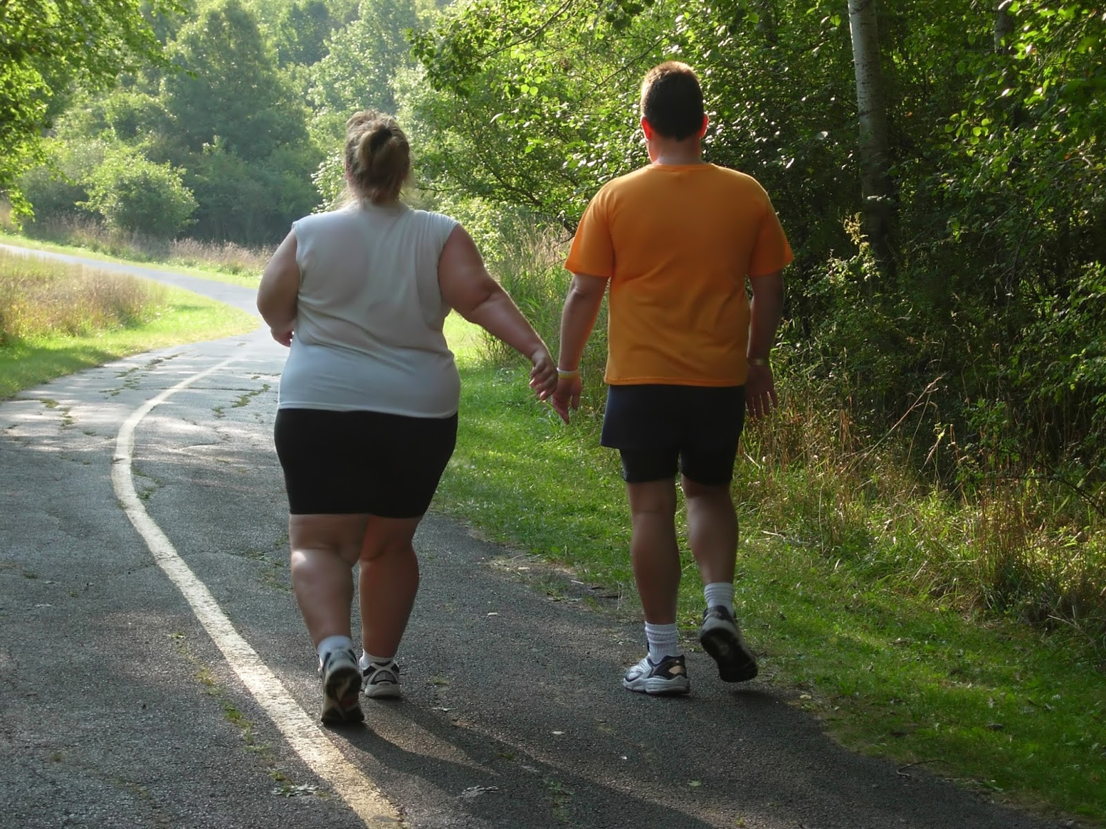 An overweight couple getting exercise and walking outside