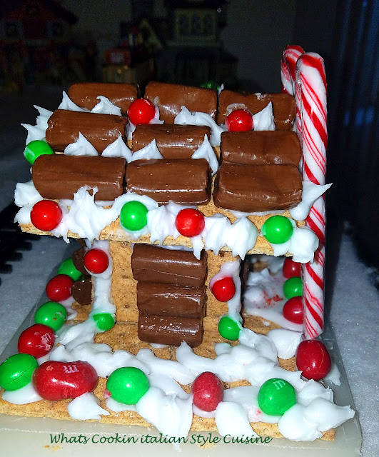 this is an adorable little house kids can make their own individual personalized  at Christmas with the candy cans, colored coated green and red candy, santa, marshmallows, graham crackers with cinnamon, powdered sugar frosting that is the glue,and tootsie rolls for the look of a log cabin