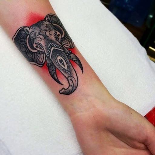 Um elefante retrato é embelezado com mandala elementos e ilustrado sobre um fundo vermelho.