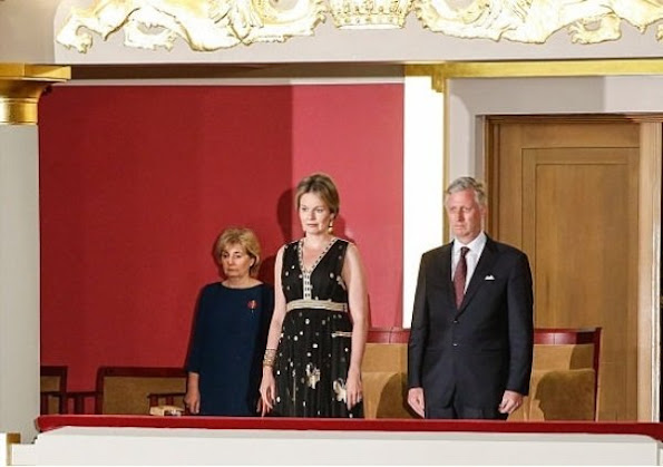 Queen Mathilde at Queen Elisabeth Piano Competition. Queen Mathilde wears Diane Von Furstenberg - DVF Vivanette Embroidered Tulle Goddess Gown. A Bag with a Story Clutch, TIKLI JEWELRY Gold Drop Earrings and Bracelet